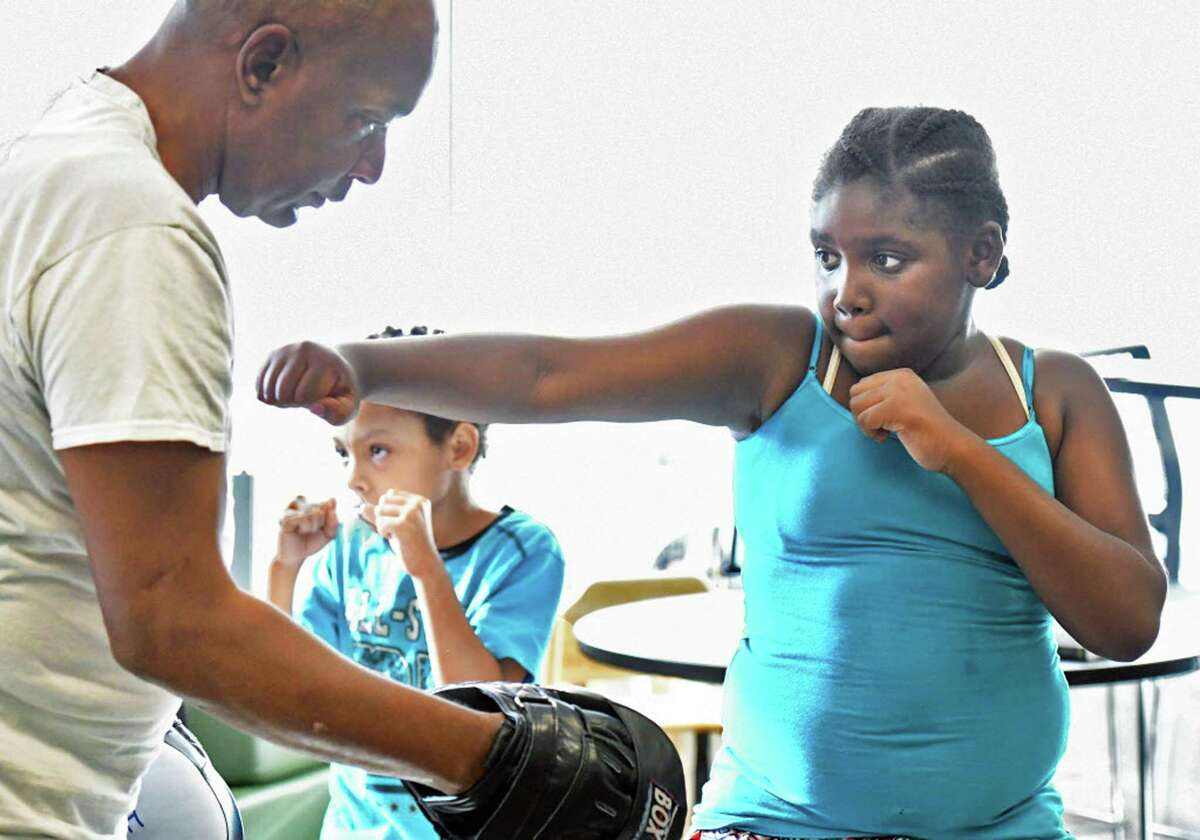 Boxing instructor Kenny Walker works with Azaria Frazier, 10, during the new program for kids designed to teach them boxing skills, confidence and discipline at Unity House Wednesday August 30, 2017 in Troy, NY. (John Carl D'Annibale / Times Union)