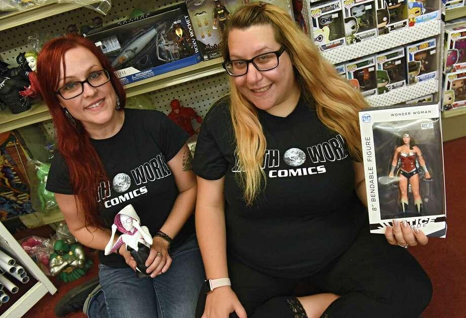 Employees Alicia Messineo, left, holds a Spider-Gwen figure and Amanda Furfaro holds a Wonderwoman figure at Earthworld Comics on Tuesday, Sept. 19, 2017 in Albany, N.Y. (Lori Van Buren / Times Union) Photo: Lori Van Buren / 20041581A