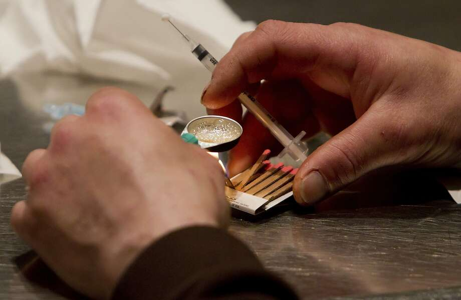 A man prepares heroin. (Darryl Dyck/The Canadian Press via AP, File) Photo: Darryl Dyck, Associated Press