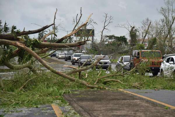 A tree blocks a street in Guaynabo in San Juan, Puerto Rico, on September 21, 2017. Puerto Rico braced for potentially calamitous flash flooding on Thursday after being pummeled by Hurricane Maria which devastated the island and knocked out the entire electricity grid.