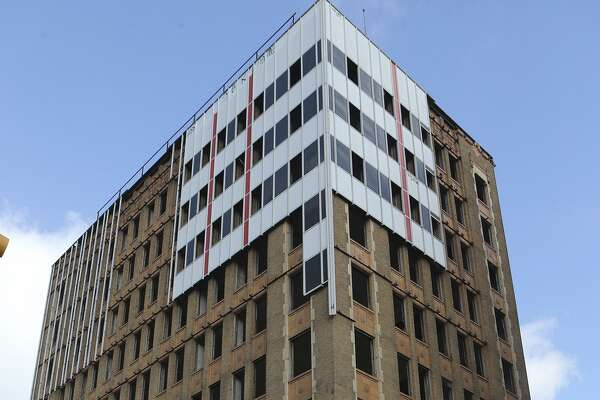 Workers have removed most of the 1960s aluminum cladding from the downtown Hedrick Building to reveal its 1928 limestone and terra cotta facade underneath.