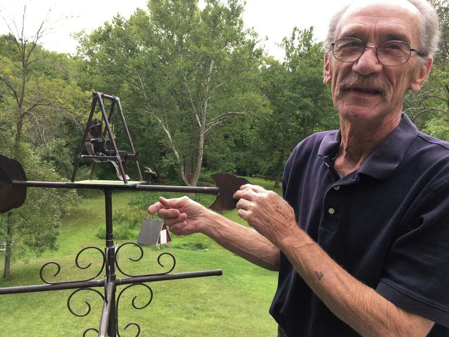 "Al Ferris Jr. gives the grandma in his ""Grandma Swings"" weather vane a push at his studio in New Milford. Ferris has made whimsical and utilitarian objects out of copper for decades. Photo: Christina Hennessy / Hearst Connecticut Media / Connecticut Post"