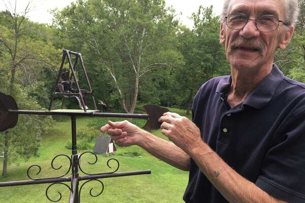 "Al Ferris Jr. gives the grandma in his ""Grandma Swings"" weather vane a push at his studio in New Milford. Ferris has made whimsical and utilitarian objects out of copper for decades."