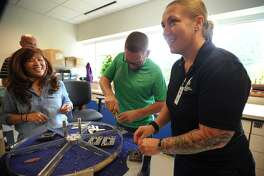With the help of Victorinox employee Tuyen Nguyen, left, Wounded Warriors Manuel Colon, of Orlando, FL, and Angela Peacock, of St. Louis, MO, assemble their contest winning Swiss Army knife designs at the company's facility in Monroe, Conn. on Thursday, September 21, 2017.