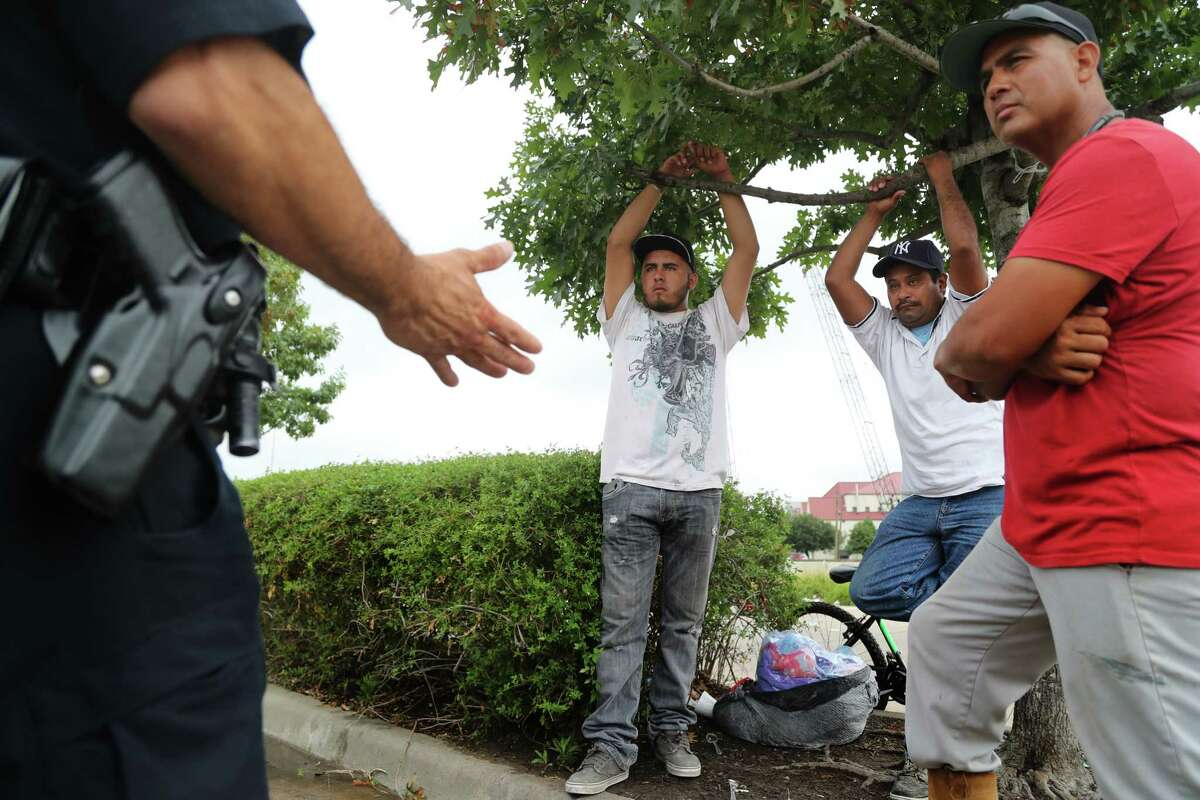 """Houston Police Department officer Al Yanez, left, 51, speaks to day laborers at Home Depot, Fabian Mendoza, right, 42, a green card holder, Orlando Rodas, center, 36, an undocumented immigrant and Pedro Galan, 20, a U.S. resident about the role of the HPD, Tuesday, Aug. 8, 2017, in Houston. Yanez answered questions related to the Texas law, known as Senate Bill 4, which bans é?'sanctuary cities.é?"""" The law will take effect Sept. 1. ( Marie D. De Jesus / Houston Chronicle )"""