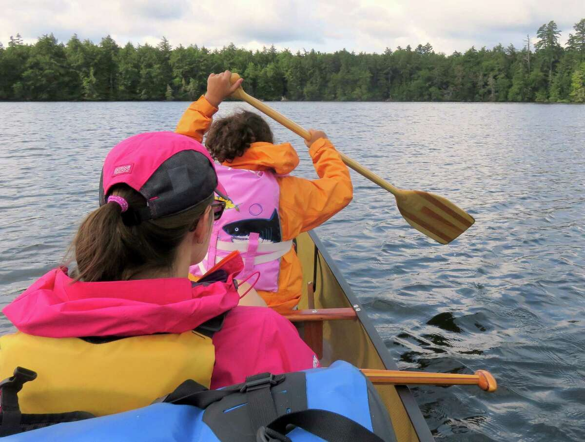 Outdoors writer Gillian Scott sits back while her foster daughter does the paddling. (Herb Terns / Times Union)