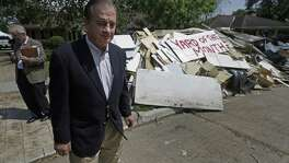 "John Sharp, Texas A&M University System chancellor and the state's new recovery czar, tours a flooded neighborhood near Westbury High School in Houston earlier this week. Homeowner David Peterson placed a sign reading ""Yard of the Month"" among the debris pile outisde his home."