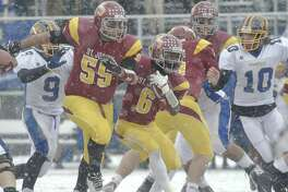 St Joseph's Mufasha Abdul Basir (6) cuts past lineman Troy Vazzano (55) during the Class M football championship game between Brookfield and St Joseph high schools at Central Connecticut State University's Arute Field in New Britain, Conn, on Saturday, December 14, 2013. Brookfield's Peter Manesis (10) moves in.