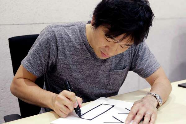 In this Sept. 14, 2017, photo, Django Co., Ltd. Director Shigetaka Kurita writes a pictograph during an interview at his office in Tokyo. The Japanese creator of the first emoji wanted to add nuance to mobile phone messages and never imagined his 1999 work would become a global phenomenon. (AP Photo/Shizuo Kambayashi)