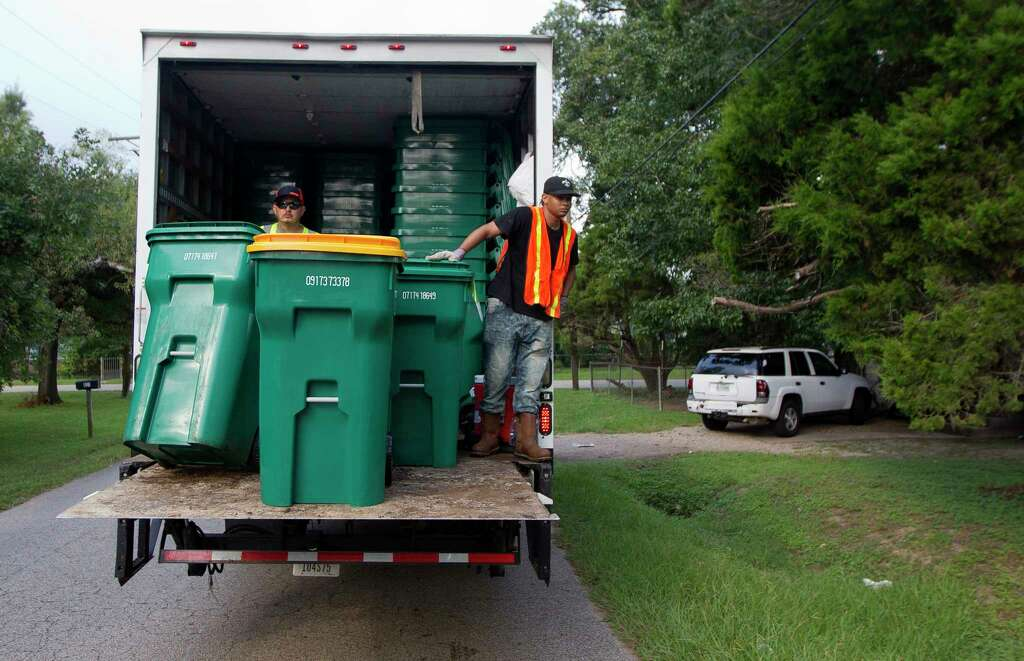 Chris Mcglory rides a truck as he helps unload new Waste Management issued recycling trash and recycle bins on Mill Avenue, Thursday, Sept. 21, 2017, in Conroe. The Conroe City Council voted in April to not renew the city's contract with long-time provider Republic Services Inc. Photo: Jason Fochtman, Staff Photographer / © 2017 Houston Chronicle