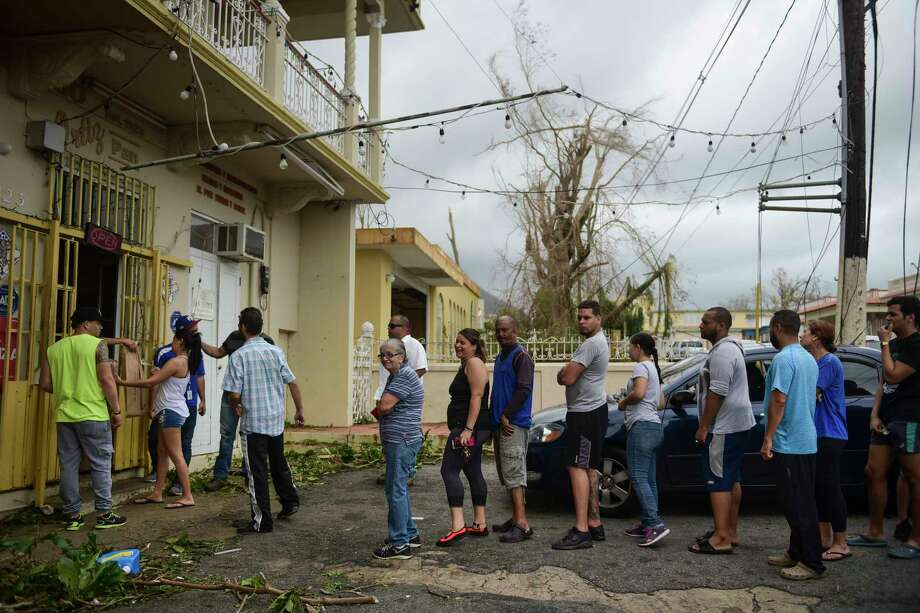 People wait in line to buy bread at Ortiz bakery after the passing of Hurricane Maria, in Yabucoa, Puerto Rico, Thursday, September 21, 2017. Photo: Carlos Giusti, STR / Copyright 2017 The Associated Press. All rights reserved.