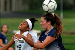 Notre Dame of Fairfield's Daryn Dickson, left, and Immaculate's Adi Chamberlin head the ball during Class M girls soccer action in Fairfield, Conn., on Thursday Sept. 21, 2016.