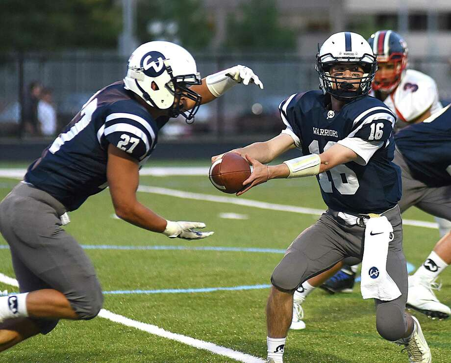 Wilton quarterback Brian Calabrese, right, hands the ball off to fullback Harvey Alexander during Friday's season-opening football game against Brien McMahon at Fujitani Field in Wilton. The host Warriors won by a 42-21 score. Photo: John Nash / Hearst Connecticut Media / Norwalk Hour