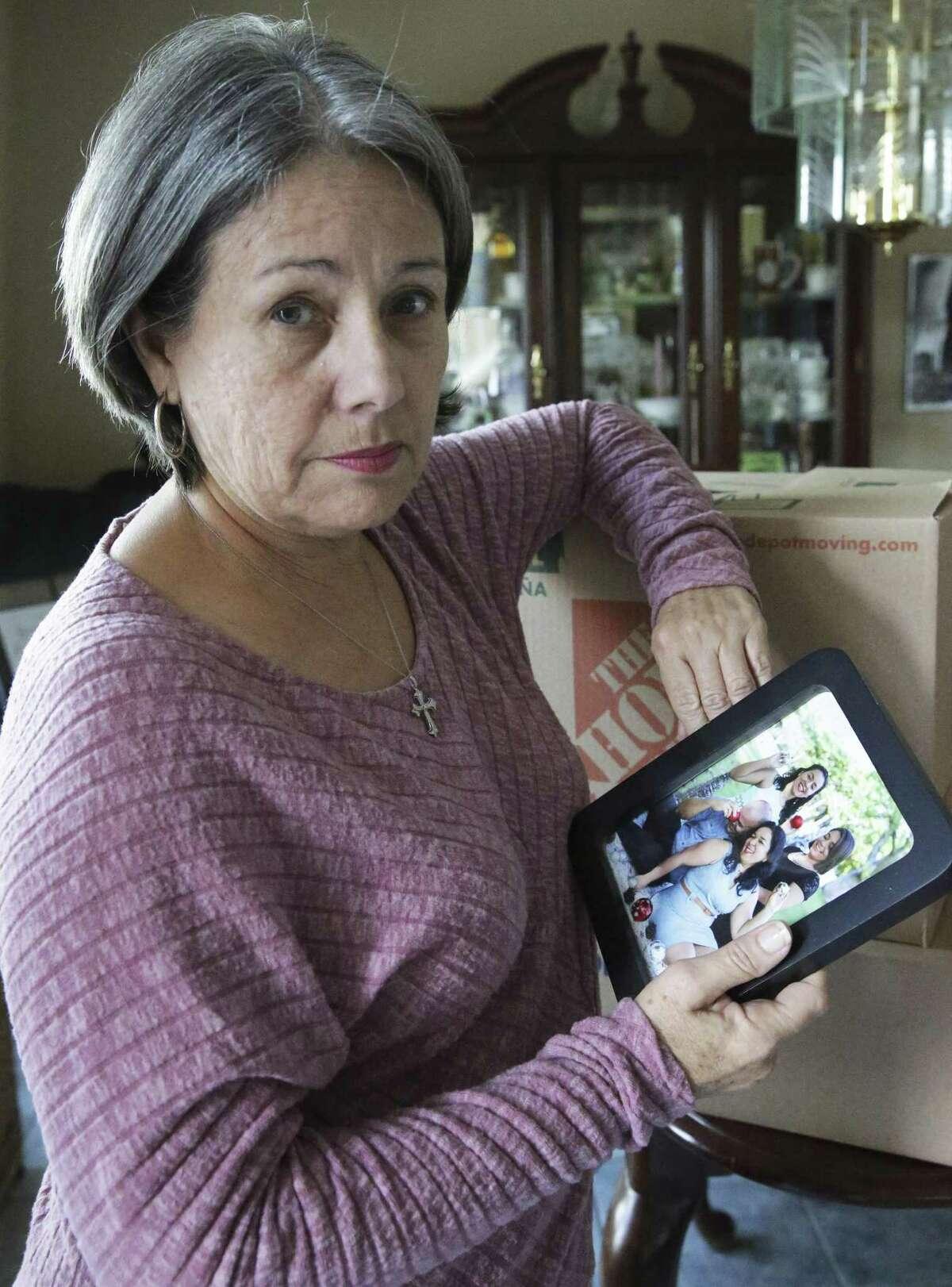 Migdalia Aponte shows a photo of family members still on the island Thursday.