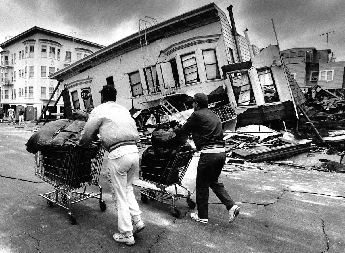 Residents walk by houses in the Marina district, severely damaged by the Loma Prieta earthquake. They were allowed 15 minutes to go in and get some of their possessions on October 20, 1989.
