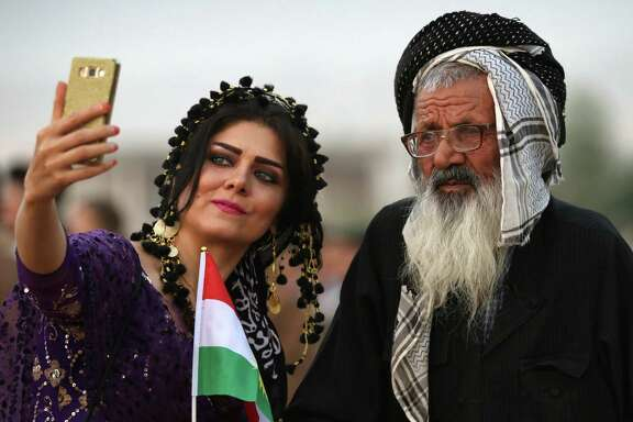 In Bahrka, Iraq, a Kurdish woman takes a selfie with a man as they take part in a rally urging people to vote in the upcoming independence referendum.