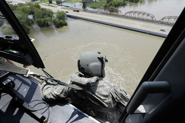 U.S. Army National Guard Staff Sgt. Drew Gleason looks for flood victims in the aftermath of Hurricane Harvey while flying over Liberty in this Sept. 1 photo. New hour-by-hour rainfall data collected by the National Weather Service shows a gauge in the city of Liberty northeast of Houston recorded 55 inches of rain during Harvey — a new record that surpasses even the 52 inches of rains from a tropical storm recorded in Hawaii in 1950.
