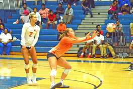 Edwardsville senior Rachel Pranger, right, makes a dig during the second game of Thursday's match at East St. Louis as teammate Megan Woll looks on.