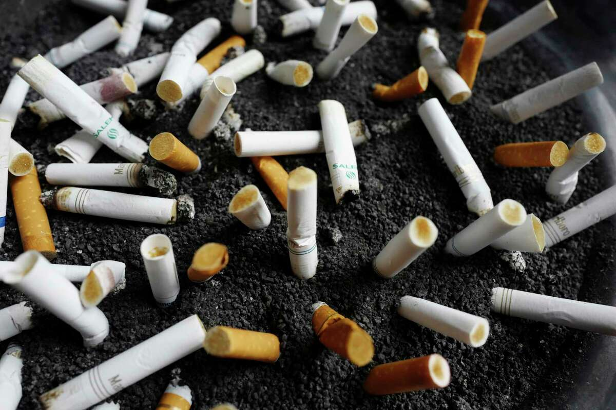 FILE - In this April 7, 2017, file photo, cigarette butts are discarded in an ashtray outside a New York office building. (AP Photo/Mark Lennihan, File)