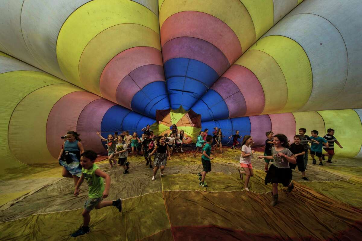 Elementary school students get a chance to walk inside a decommissioned hot air balloon during a demonstration at the Harrison Avenue Elementary School Thursday Sept. 21, 2017 in South Glens Falls, N.Y. The display of balloons was part of the 45th Annual Adirondack Balloon Festival which takes place this weekend in Glens Falls. (Skip Dickstein/Times Union)