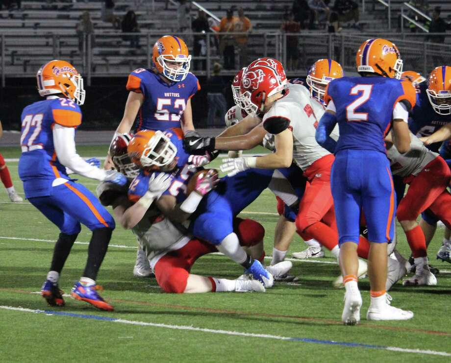 The New Canaan defense swarms to make a tackle against Danbury last week. Photo: Anthony E. Parelli / Hearst Connecticut Media / New Canaan News