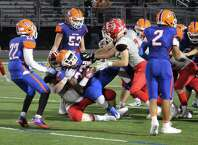 The New Canaan defense swarms to make a tackle against Danbury last week.