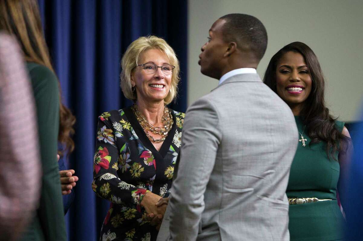 Betsy DeVos, secretary of education, greets an HBCU All Star student during a White House summit on Historically Black Colleges and Universities, in the Eisenhower Executive Office Building at The White House in Washington, Sept. 18, 29017. Students who apply and are selected for the Department of Education program serve for one year as ambassadors of the White House Initiative on HBCUs. At right is Omarosa OnŽe Manigault-Newmanon, a political aide in President Trump's administration. (Tom Brenner/The New York Times) ORG XMIT: XNYT60