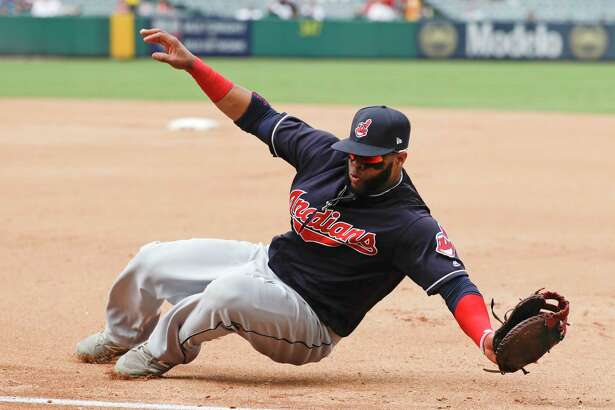 Cleveland Indians first baseman Carlos Santana fields a ball hit down the first base line by Los Angeles Angels' Kole Calhoun during the fourth inning of a baseball game in Anaheim, Calif., Thursday, Sept. 21, 2017. Calhoun was out at first. (AP Photo/Chris Carlson) ORG XMIT: ANS110