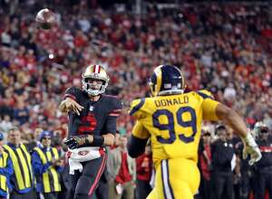 San Francisco 49ers' Brian Hoyer passes in 4th quarter against Los Angeles Rams' Aaron Donald during Rams' 41-39 win in NFL game at Levi's Stadium in Santa Clara, Calif., on Thursday, September 21, 2017.