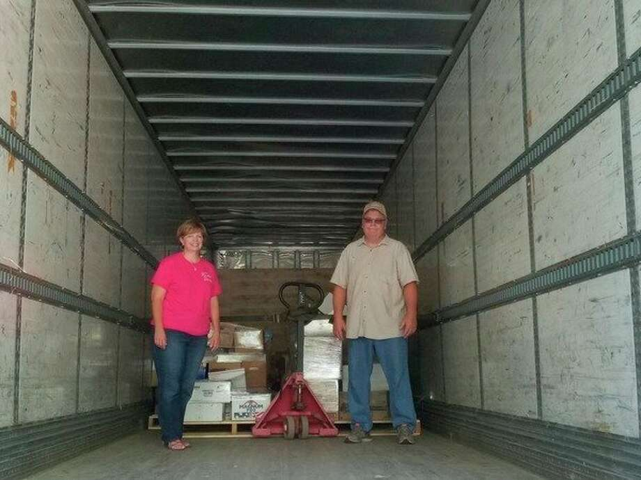 Diana and Charles Bennett load their Bennett Farms semi-truck to take more than 10,000 books, school supplies and more to Katy, Texas, along with 100 bales of hay. Neither have been to Texas, but their first trip is one of need for six elementary schools, one that had its library swallowed up by Hurricane Harvey. (Tereasa Nims/for the Daily News)