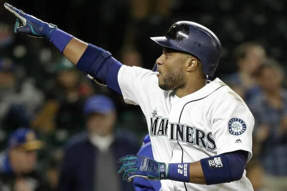 Seattle Mariners' Robinson Cano points to the stands as he crosses home on his solo home run against the Texas Rangers in the ninth inning of a baseball game Thursday, Sept. 21, 2017, in Seattle. The homer was the 300th of Cano's career. (AP Photo/Elaine Thompson)