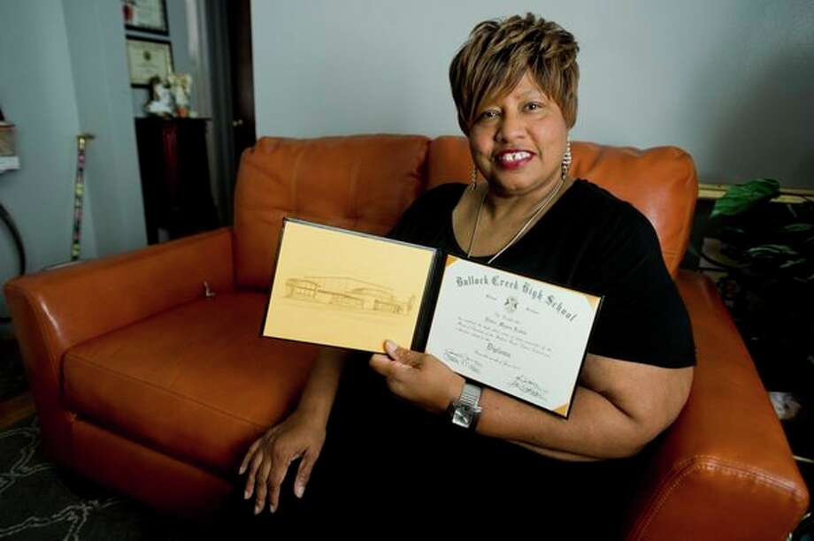 Debra Lewis poses for a portrait with her high school diploma from Bullock Creek High School inside her home. Lewis, a 62-year-old Midland resident, recently graduated with her high school diploma after 40 years of setbacks. (Katy Kildee/kkildee@mdn.net)