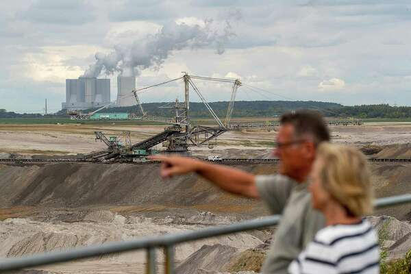 A giant excavator operates at the Schleenhain open cast lignite mine, operated by Mibrag GmbH, as the Lippendorf brown coal-fired power plant, operated by Vatenfall AB, stands beyond, near the village of Poedelwitz, Germany, on Wednesday, Sept. 6, 2017. By 2030, the eastern German town of Poedelwitz will likely be razed to get at the rich veins of coal beneath its half-timbered houses. Photographer: Krisztian Bocsi/Bloomberg