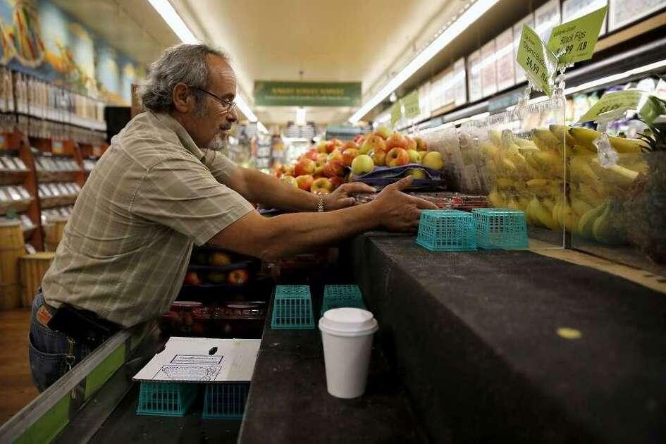 Gus Vardakastanis puts strawberries on display at Haight Street Market in San Francisco. Vardakastanis died in a hit-and-run incident Friday.