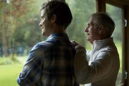 Thoughtful father and son looking through window in cottage