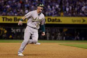 Oakland Athletics' Josh Donaldson celebrates as he rounds the bases on a three-run home run by teammate Brandon Moss during the sixth inning of the AL wild-card playoff baseball game against the Kansas City Royals Tuesday, Sept. 30, 2014, in Kansas City, Mo. The home run was Moss' second of the game. (AP Photo/Jeff Roberson)
