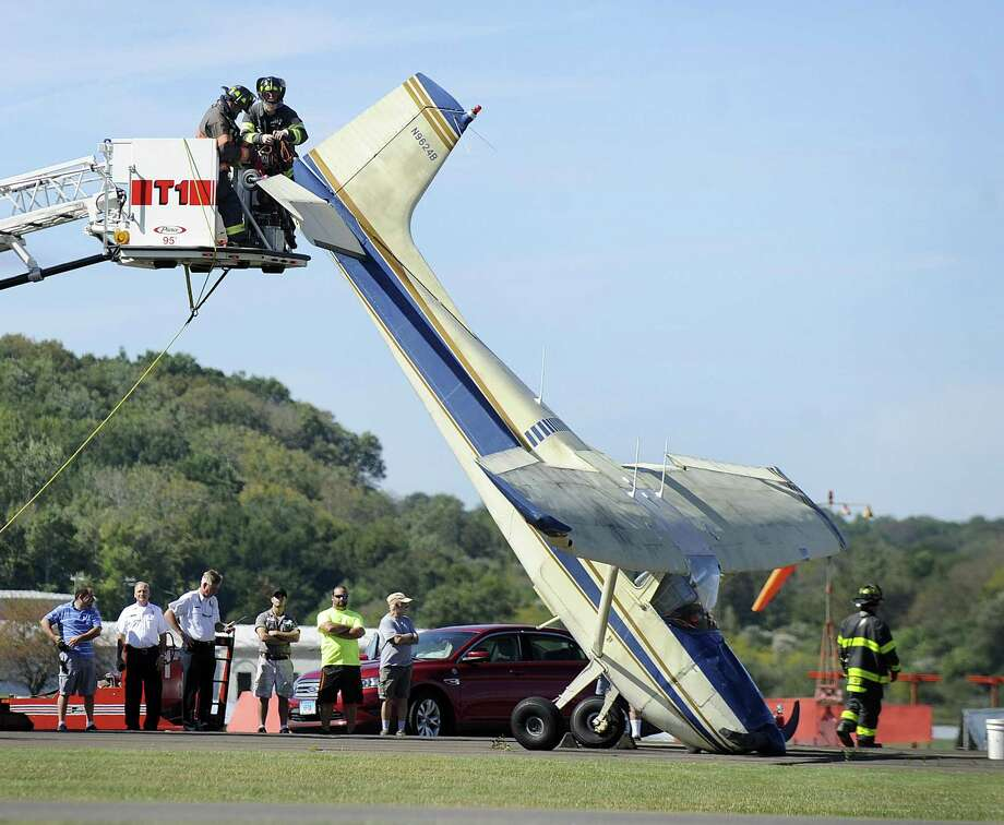 The Danbury Fire Department hooks up the tail of a plane in order to lower it Friday after the pilot experienced a rough landing at Danbury Airport, Friday, Sept. 22, 2017. Photo: Carol Kaliff / Hearst Connecticut Media / The News-Times