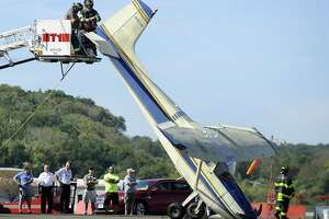 The Danbury Fire Department hooks up the tail of a plane in order to lower it Friday after the pilot experienced a rough landing at Danbury Airport, Friday, Sept. 22, 2017.