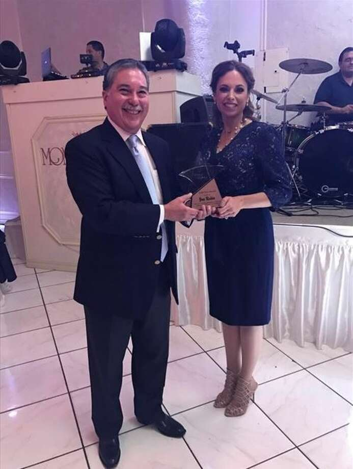Veronica Cuellar, president of the local nonprofit Star of Hope, presents the group's Gold Star Award to former Webb County District Attorney Joe Rubio on Thursday night at the Montecarlo reception hall. Photo: Courtesy