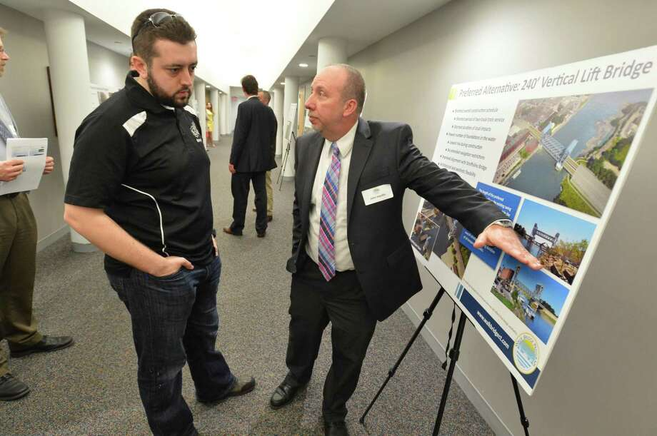 During a public informational meeting at City Hall on Wednesday April 12, 2017 in Norwalk Conn, John Hanifin, Project Manager with DOT talks about the vertical lift bridge as a replacement for the walk bridge with Konstantinos Kousidis. His business is directly impacted by the project, his shop Thinq Mac in SoNo is next to the Metro North tracks and the walk bridge. Photo: Alex Von Kleydorff / Hearst Connecticut Media / Norwalk Hour