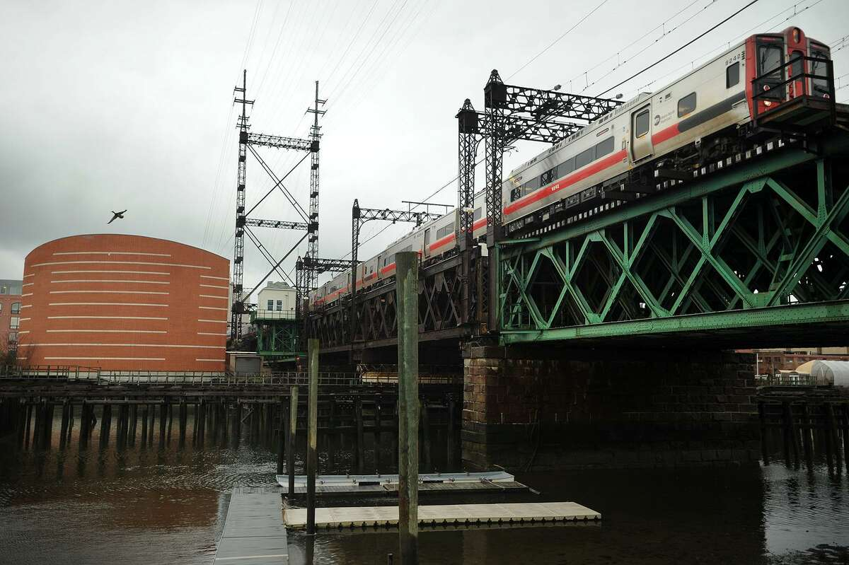 A Metro North train heading east crosses the Walk Bridge over the Norwalk River in Norwalk, Conn. on Tuesday, April 12, 2016. The bridge, which bisects the Norwalk Aquarium, at left, is scheduled to be replaced.