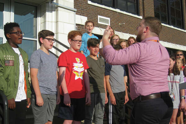 """Under the direction of Tom O'Malley, right, the Lincoln Middle School Chorus performs the """"Star Spangled Banner"""" during the Constitution Week Celebration."""