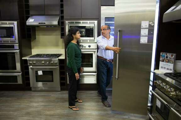 Gana and Aruna Mahendravada shop for new kitchen appliances at the Best Buy store on Richmond Avenue near 610, Thursday, Sept. 21, 2017. The Mahendravada's home in Bellaire flooded with ten inches of water last month. The home was raised after Tropical Storm Allison, and the family had never seen the house flood in the ten years they have lived there. (Mark Mulligan / Houston Chronicle)