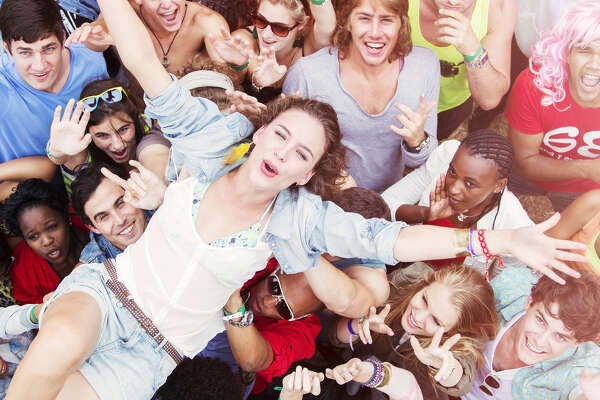 Enthusiastic woman crowd surfing at music festival