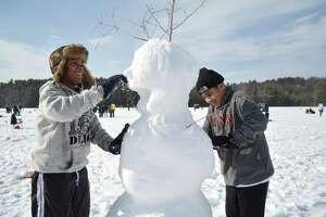 Pedro Dejesus, 13, and Louis Vega, 12, of Hartford, build a snowman Saturday during the DEEP-sponsored 'No Child Left Inside' event at Burr Pond State Park in Torrington. (Tom Caprood-Register Citizen)