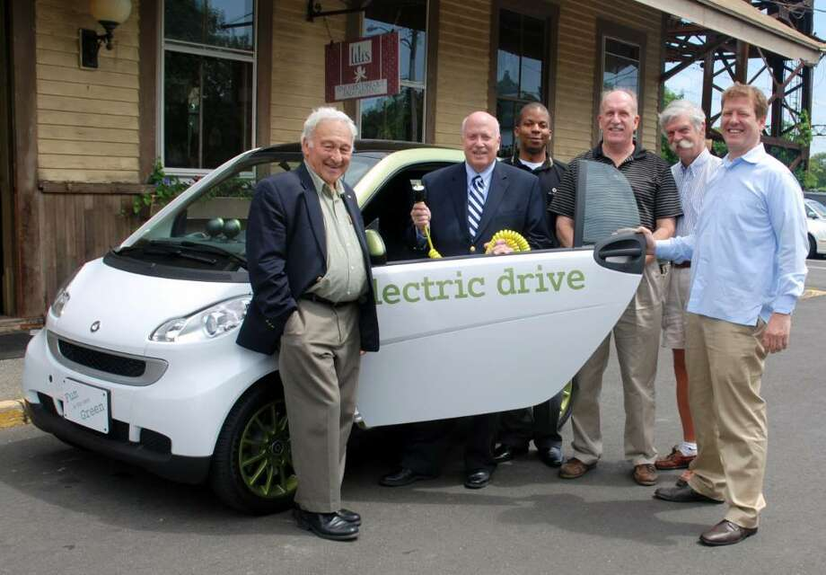 Westporters involved in a project to bring electric car charging stations to the Westport Metro-North Station test drove the smartfortwo electric car. Pictured (l-r) are Leo Cirino, First Selectman Gordon Joseloff, Eric Mitchell, brand manager at the Smart center in Fairfield, Building Official Steve Smith, Carl Leaman, and Rick Hoag. Photo: Contributed Photo / Westport News