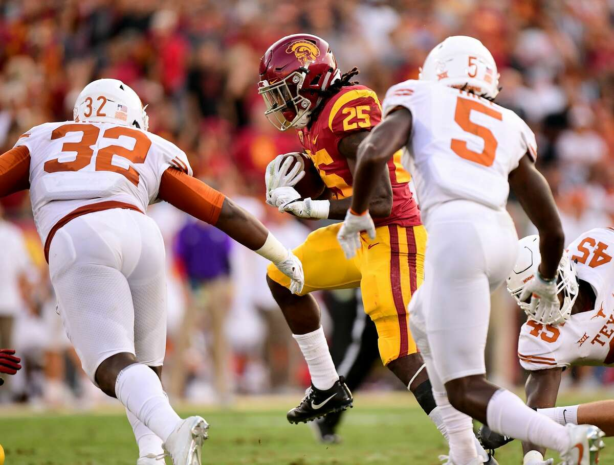 LOS ANGELES, CA - SEPTEMBER 16: Ronald Jones II #25 of the USC Trojans attempts to avoid a tackle from Malcolm Roach #32 and Holton Hill #5 of the Texas Longhorns at Los Angeles Memorial Coliseum on September 16, 2017 in Los Angeles, California. (Photo by Harry How/Getty Images)
