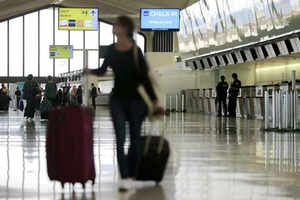 A traveler looks at an information board as officials, far right, stand guard at Newark Liberty International Airport, Wednesday, June 29, 2016, in Newark, N.J. Following the Istanbul terrorist attack on Tuesday, travel experts say still take that vacation but always be valiant about surroundings. A few key tricks can help to make the trip safer. (AP Photo/Julio Cortez)