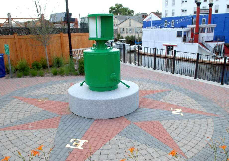 A green buoy sits atop the compass in the pocket park off South Water Street, Byram, Wednesday afternoon,  June 23, 2010. Photo: Bob Luckey / Greenwich Time