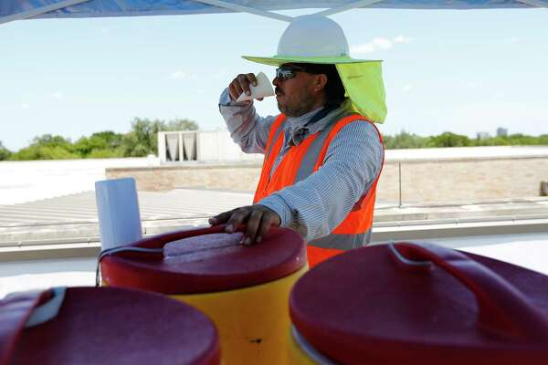 Guillermo Munoz takes a drink of water as Beldon Roofing workers take on a job at Sunshine Cottage during the heat of the day on Friday, July 21, 2017.